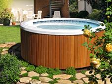 Гидромассажный бассейн спа Arena на мощеной площадке около открытого плавательного бассейна.